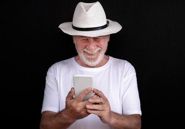 Portret van senior bebaarde man die lacht in videogesprek met slimme telefoon op zwarte achtergrond