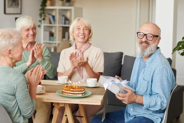 Portret van senior bebaarde man geschenkdoos houden en glimlachen naar de camera terwijl zijn vrienden hem feliciteren aan de tafel