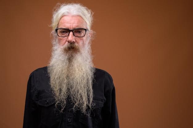 Portret van senior bebaarde man op bruin