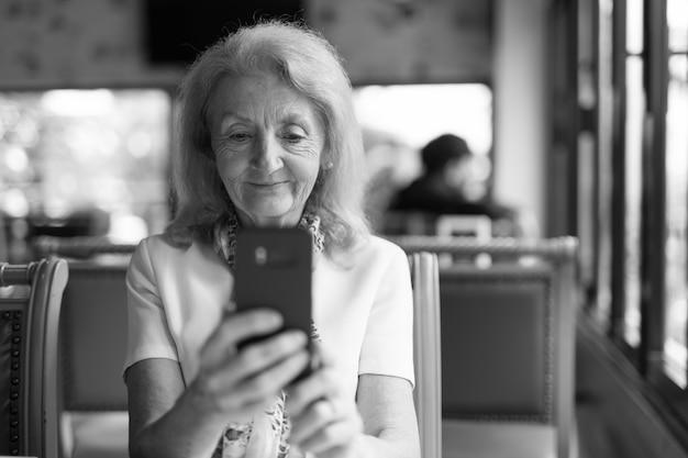 Portret van senior bejaarde vrouw met behulp van mobiele telefoon