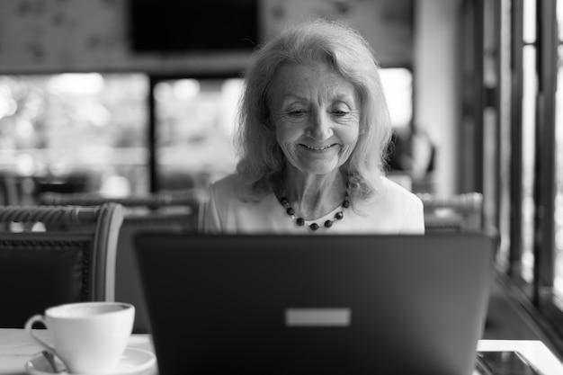 Portret van senior bejaarde vrouw zitten en met behulp van laptop computer