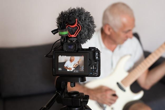 Portret van senior blogger gitaarspelen vanuit zijn huis opnamestudio