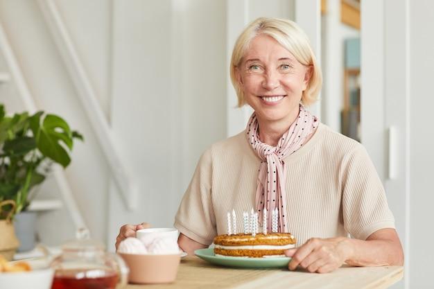 Portret van senior blonde haren glimlachend in de camera zittend aan tafel met thee en cake Premium Foto