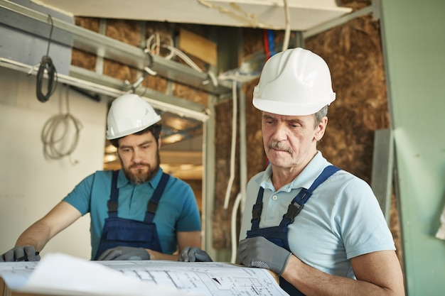 Portret van senior bouwvakker veiligheidshelm dragen tijdens het kijken naar plattegronden tijdens het renoveren van huis, kopie ruimte