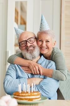 Portret van senior en gelukkige familie van twee glimlachend in de camera zittend aan tafel met cake en verjaardag vieren