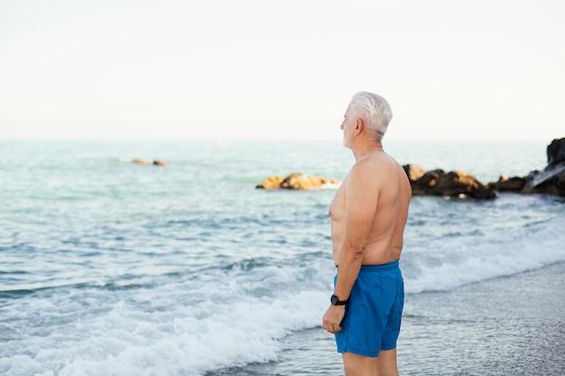Portret van senior grijsharige man op het strand
