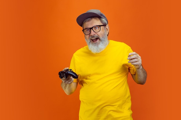 Portret van senior hipster man met behulp van apparaten, gadgets geïsoleerd op oranje studio achtergrond. tech en vreugdevolle ouderen levensstijl concept. t