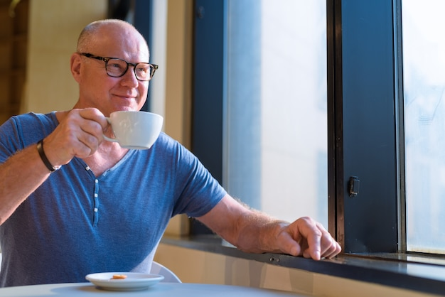 Portret van senior knappe scandinavische toeristische man ontspannen in de coffeeshop