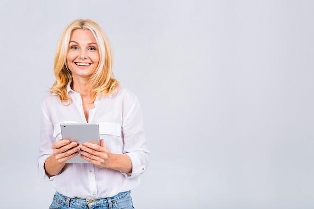Portret van senior leeftijd rijpe blonde vrouw met tablet pc, geïsoleerd op een witte achtergrond.