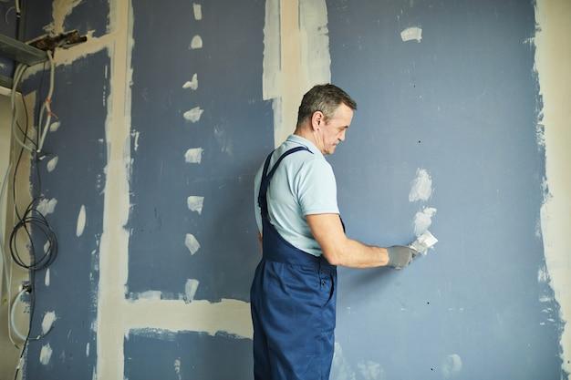 Portret van senior man aan het werk op droge muur tijdens het renoveren van huis, kopie ruimte