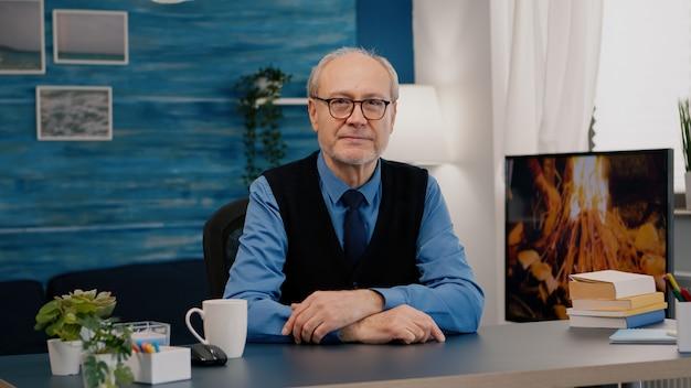 Portret van senior man chatten en luisteren op afstand teamwork tijdens video-oproep thuiswerken. een bejaarde die internet online chattechnologie-webcam gebruikt, maakt een virtuele vergaderingsoproepverbinding