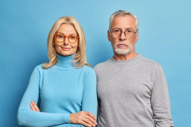 Portret van senior man en vrouw gepensioneerden staan dicht bij elkaar gekleed in vrijetijdskleding en een bril genieten van zoete momenten van samenzijn of pensioen geïsoleerd over blauwe muur