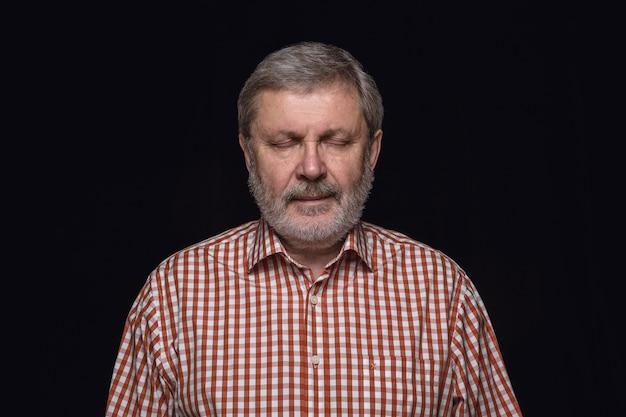 Portret van senior man geïsoleerd op zwarte ruimte close-up. denken en glimlachen