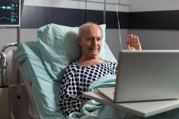 Portret van senior man groet familie zwaaien naar laptop camera leggen in ziekenhuisbed, na diagnose van de ziekte, ademhaling met zuurstofbuis. moderne apparatuur die de hartslag van de patiënt bewaakt tijdens herstel