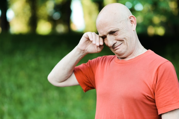 Portret van senior man huilen en kijken naar camera met rode ogen close-up