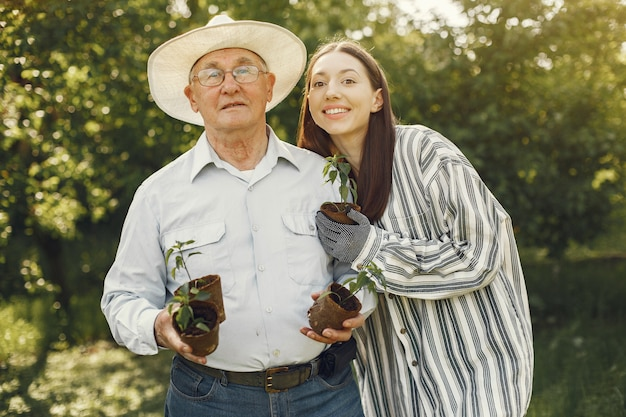 Portret van senior man in een hoed tuinieren met kleindochter