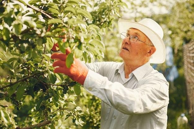 Portret van senior man in een hoed tuinieren