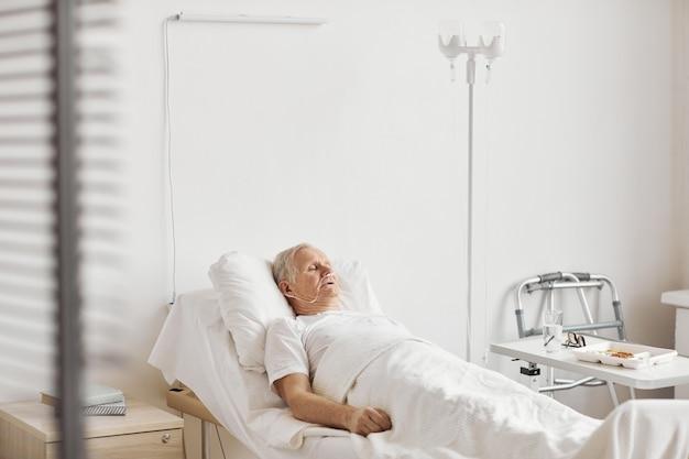 Portret van senior man liggend op bed in witte ziekenhuiskamer met iv infuus en zuurstofondersteuning, kopieer ruimte