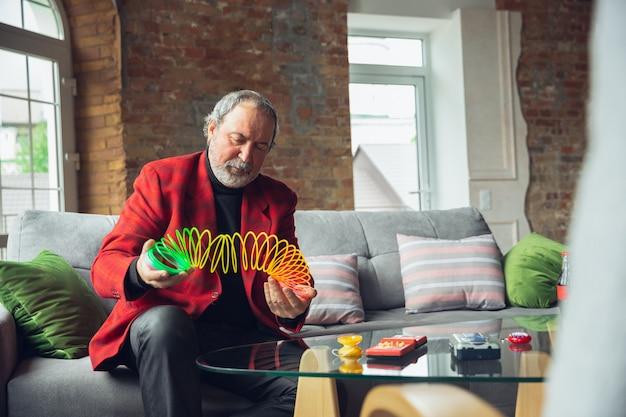 Portret van senior man met behulp van retro dingen, speelgoed, dingen uit het verleden ontmoeten