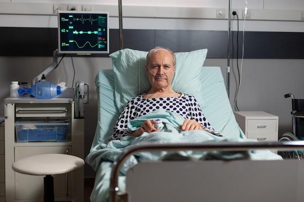 Portret van senior man patiënt rusten in ziekenhuisbed