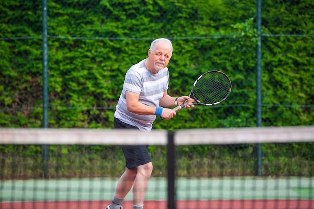 Portret van senior man tennissen in een buiten, gepensioneerde sport, sport concept