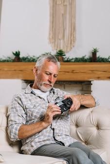 Portret van senior man zit op de bank op zoek naar de camera