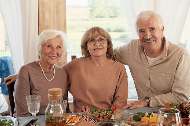 Portret van senior mensen lachend zittend aan de tafel thuis