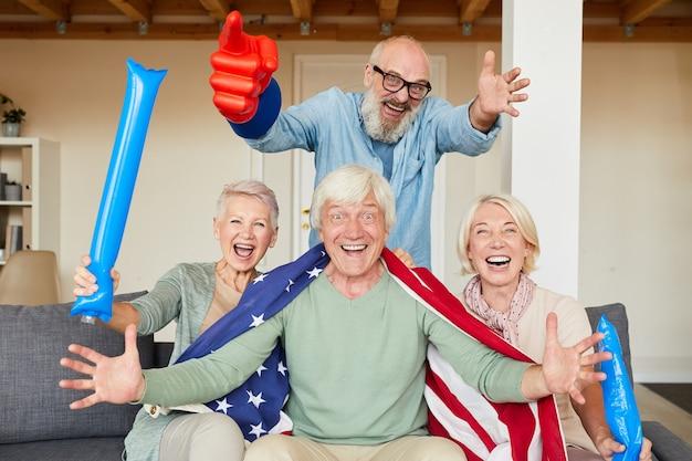 Portret van senior mensen zittend op de bank en juichen voor hun favoriete voetbalteam thuis