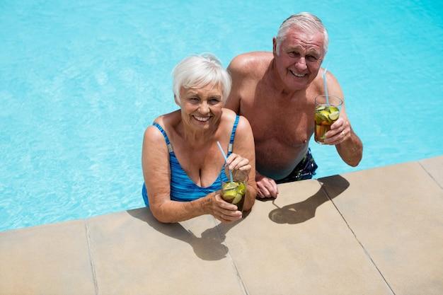 Portret van senior paar bedrijf glazen ijsthee in zwembad