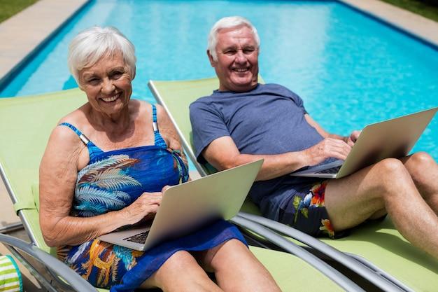 Portret van senior paar met laptop op lounge stoel bij zwembad