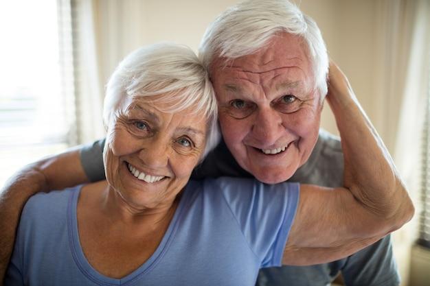 Portret van senior paar omhelzen elkaar in de slaapkamer thuis
