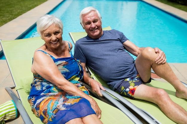 Portret van senior paar ontspannen op luie stoel bij zwembad