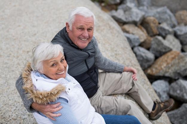 Portret van senior paar zittend op rots op het strand