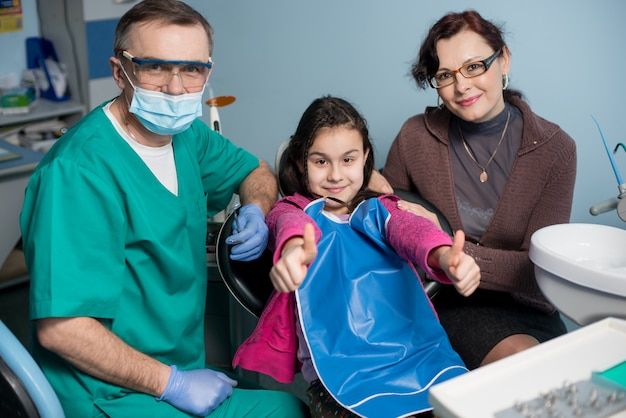 Portret van senior pediatrische tandarts en meisje met haar moeder op het eerste tandheelkundige bezoek aan de tandartspraktijk. jonge patiënt lacht, duimen opdagen. tandheelkunde, geneeskunde en gezondheidszorg concept