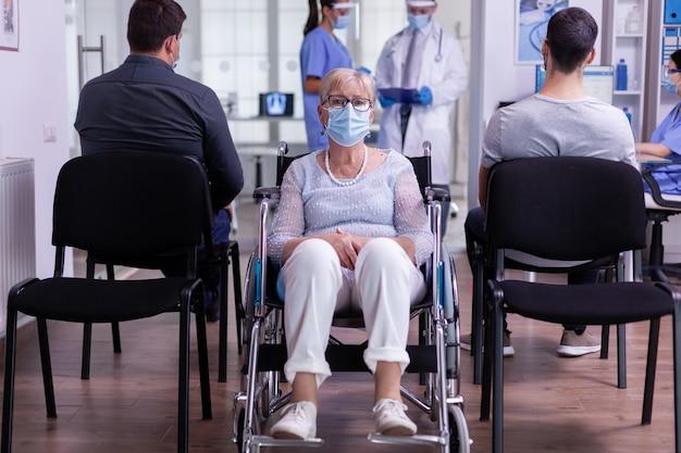 Portret van senior verlamde, gehandicapte vrouw met gezichtsmasker tegen coronavirus zittend in rolstoel kijkend naar camera in recepties reception