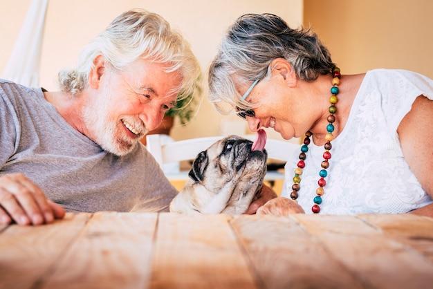 Portret van senior volwassen blanke mensen paar met grappige pug hond zoenen en hebben