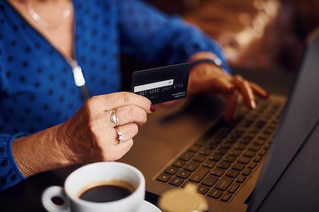 Portret van senior vrouw die binnen in het café zit met moderne laptop en creditcard in de hand.