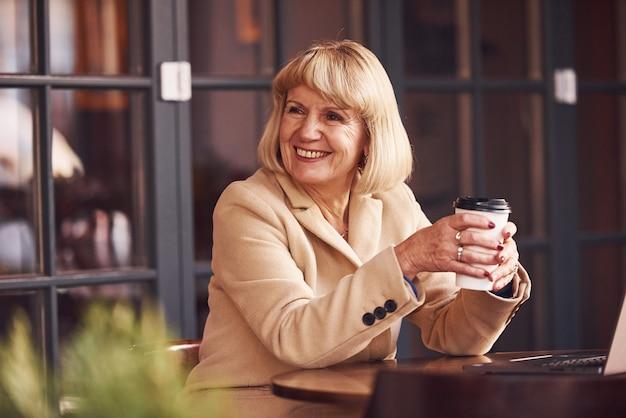 Portret van senior vrouw die binnen in het café zit met moderne laptop en kopje drank in handen.