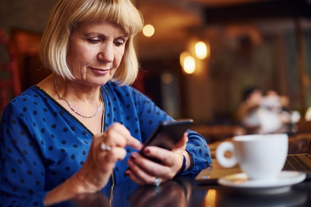 Portret van senior vrouw die binnen in het café zit met moderne laptop.