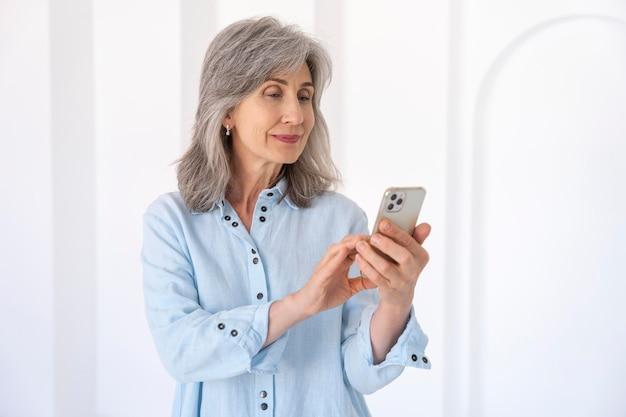 Portret van senior vrouw die smartphone-apparaat gebruikt