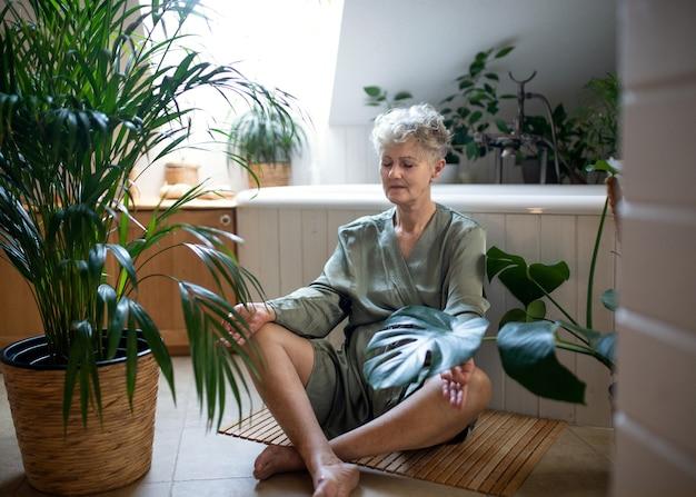 Portret van senior vrouw die thuis yoga doet in de badkamer, ontspan en zelfzorgconcept.