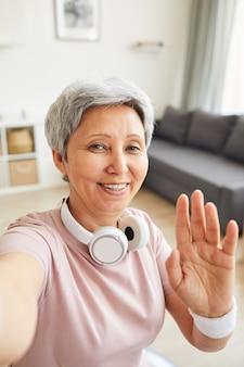 Portret van senior vrouw glimlachend in de camera en haar hand zwaaien zegt ze hallo