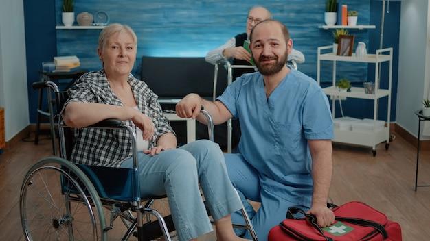 Portret van senior vrouw in rolstoel en man verpleegster