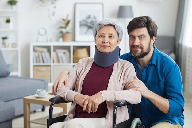 Portret van senior vrouw in verband op haar nek zittend in rolstoel met verpleger thuis