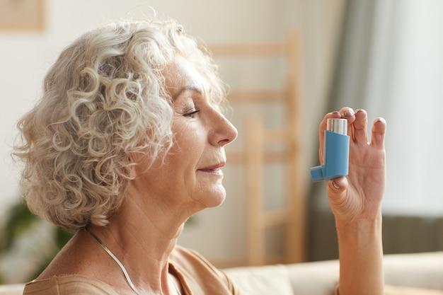 Portret van senior vrouw met behulp van inhalator voor astma of ademhalingsproblemen in thuissituatie