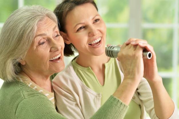 Portret van senior vrouw met dochter die thuis op microfoon zingt