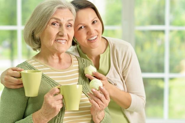 Portret van senior vrouw met dochter met thee thuis