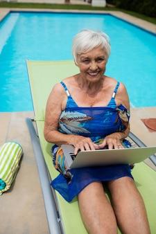 Portret van senior vrouw met laptop op lounge stoel bij zwembad