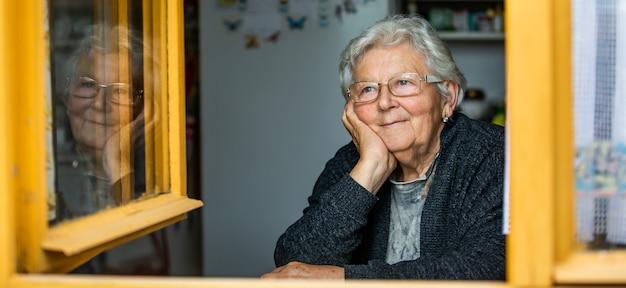 Portret van senior vrouw of grootmoeder kijken uit het raam en glimlachen