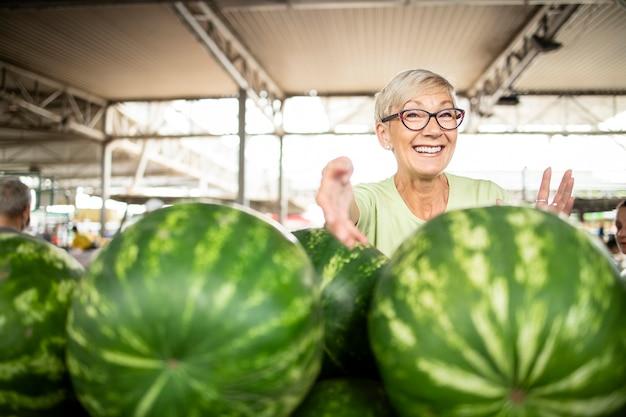 Portret van senior vrouw verkoper op de markt die verse biologische watermeloenen verkoopt.
